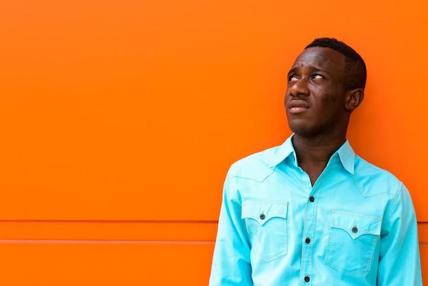 Jeune homme africain noir pensant tout en regardant contre orange