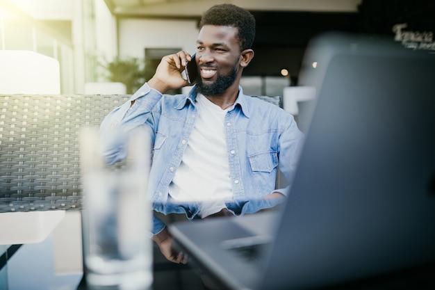 Jeune homme africain parlant de téléphone alors qu'il était assis avec un ordinateur portable au café
