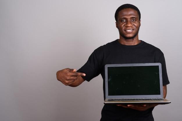 Jeune homme africain portant une chemise noire sur fond gris