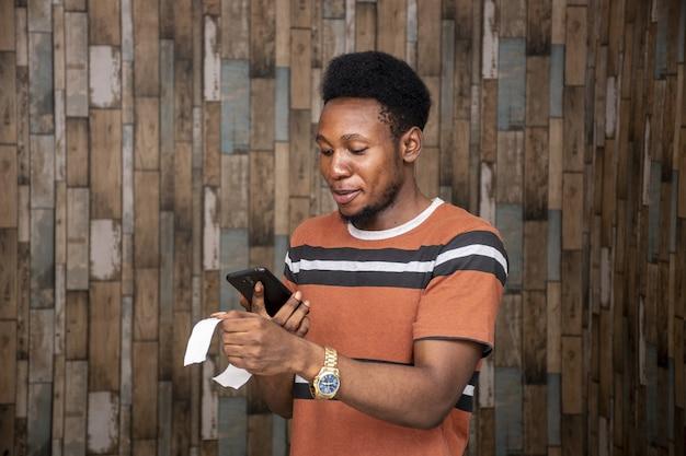 Jeune homme africain prenant une photo d'un feuillet à l'aide de son smartphone