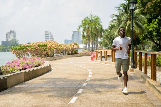 Jeune homme africain qui court à l'extérieur dans le parc