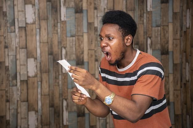 Jeune homme africain regardant un morceau de papier