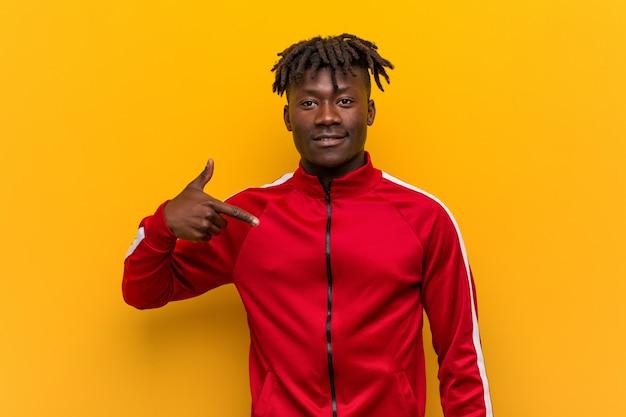 Jeune homme africain de remise en forme, pointant à la main vers un espace de copie de chemise, fier et confiant