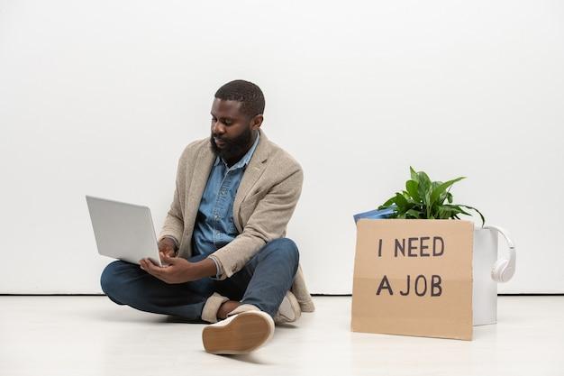 Jeune homme africain sans emploi dans des vêtements décontractés assis sur le sol par mur au bureau et à l'aide d'un ordinateur portable pour rechercher de nouveaux postes vacants sur le net