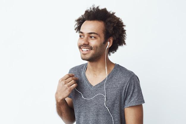 Jeune homme africain souriant éteindre un casque filaire sur un mur blanc à l'écoute des oiseaux.