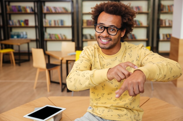 Jeune homme africain souriant utilisant une tablette et demandant l'heure à la bibliothèque