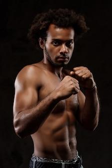 Jeune homme africain sportif posant sur le mur noir.