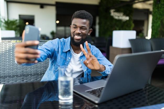 Jeune homme africain avec téléphone prendre selfie faire un geste de paix alors qu'il était assis avec un ordinateur portable au café