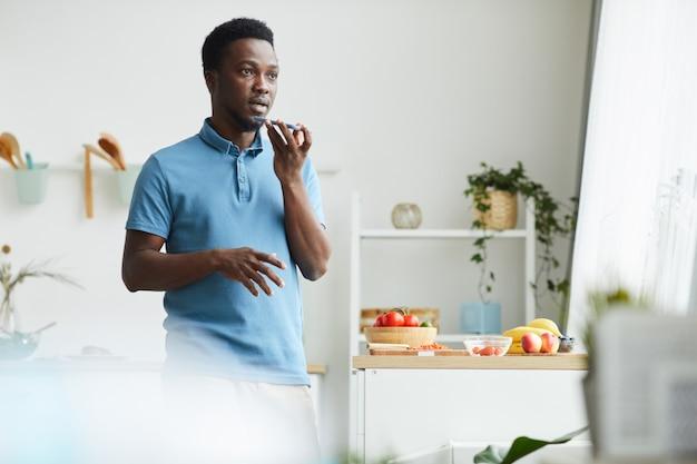 Jeune homme africain tenant un téléphone portable dans sa main et l'enregistrement d'un message audio en se tenant debout dans la pièce à la maison