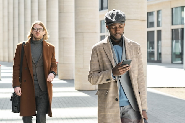 Jeune homme africain utilisant un téléphone portable en marchant le long de la rue avec un homme en arrière-plan