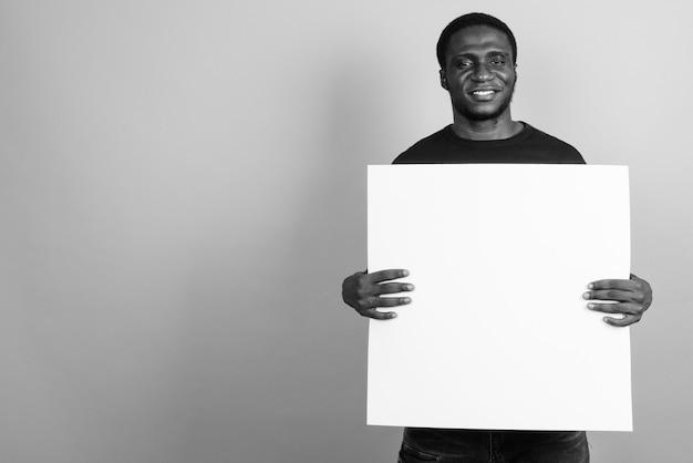 Jeune homme africain vêtu d'une chemise noire. noir et blanc