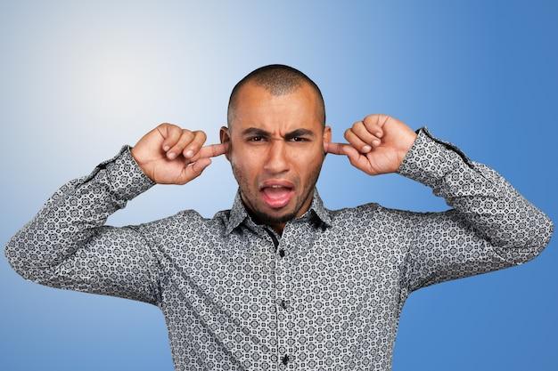 Jeune homme africain en vetu fermant ses oreilles