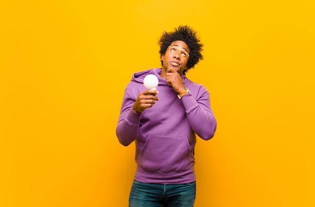 Jeune homme afro-américain avec une ampoule contre dos orange