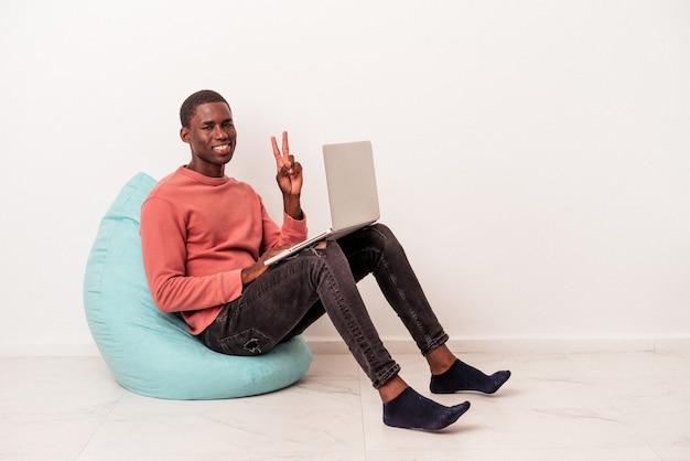 Jeune homme afro-américain assis sur une bouffée à l'aide d'un ordinateur portable isolé sur fond blanc joyeux et insouciant montrant un symbole de paix avec les doigts.
