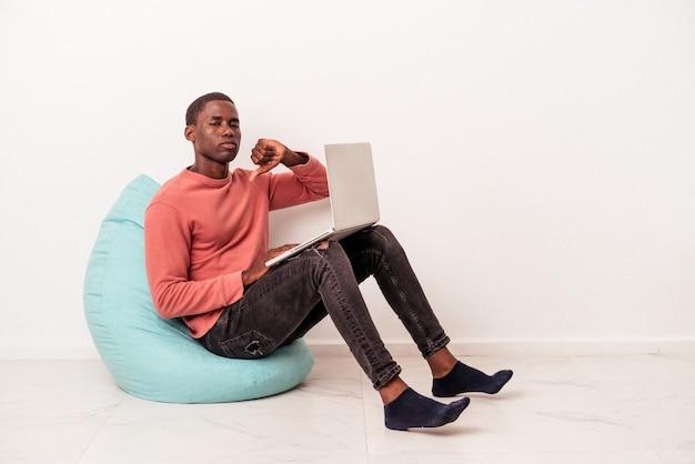 Jeune homme afro-américain assis sur une bouffée à l'aide d'un ordinateur portable isolé sur fond blanc montrant un geste d'aversion, les pouces vers le bas. notion de désaccord.