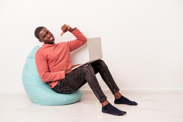 Jeune homme afro-américain assis sur une bouffée à l'aide d'un ordinateur portable isolé sur fond blanc se sent fier et confiant, exemple à suivre.