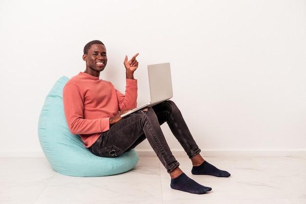 Jeune homme afro-américain assis sur une bouffée à l'aide d'un ordinateur portable isolé sur fond blanc souriant et pointant de côté, montrant quelque chose dans un espace vide.