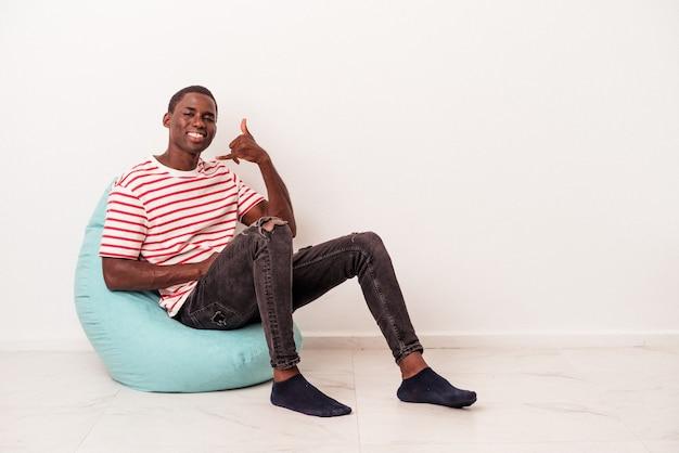 Jeune homme afro-américain assis sur une bouffée isolée sur fond blanc montrant un geste d'appel de téléphone portable avec les doigts.