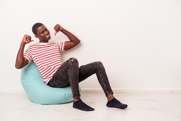 Jeune homme afro-américain assis sur une bouffée isolée sur fond blanc se sent fier et confiant, exemple à suivre.