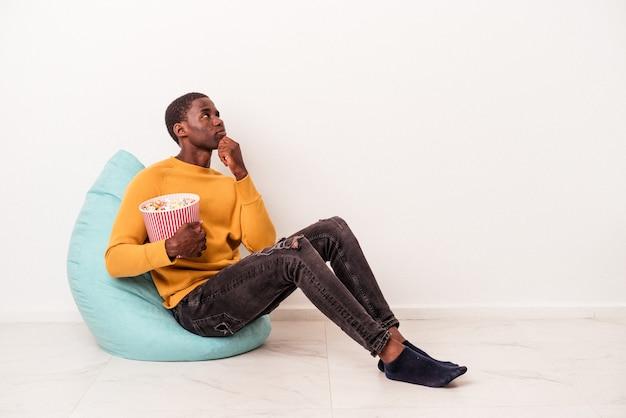 Jeune homme afro-américain assis sur une bouffée mangeant du pop-corn isolé sur fond blanc regardant de côté avec une expression douteuse et sceptique.