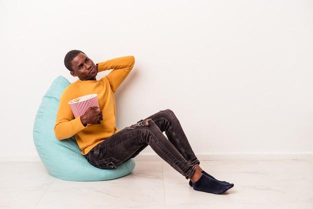 Jeune homme afro-américain assis sur une bouffée mangeant du pop-corn isolé sur fond blanc touchant l'arrière de la tête, pensant et faisant un choix.