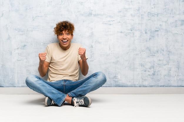 Jeune homme afro-américain assis sur le sol célébrant une victoire en position de gagnant