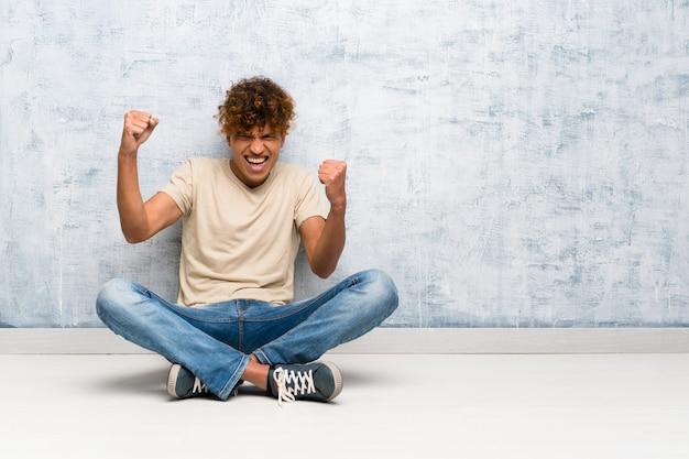 Jeune homme afro-américain assis sur le sol célébrant une victoire