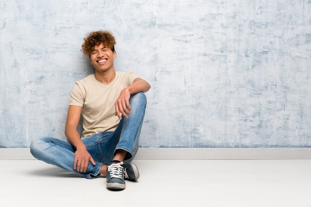 Jeune homme afro-américain assis sur le sol en gardant les bras croisés en position frontale