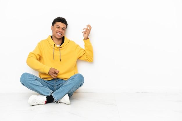 Jeune homme afro-américain assis sur le sol isolé sur fond blanc faisant un geste de guitare