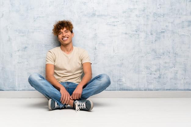 Jeune homme afro-américain assis sur le sol en riant