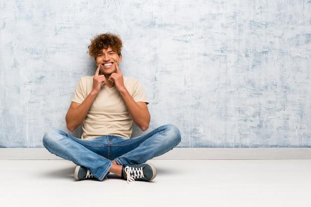 Jeune homme afro-américain, assis sur le sol, souriant avec une expression heureuse et agréable