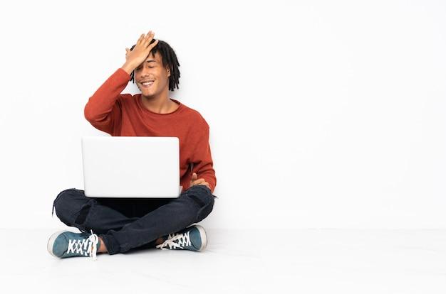 Jeune homme afro-américain assis sur le sol et travaillant avec son ordinateur portable a réalisé quelque chose et a l'intention de la solution