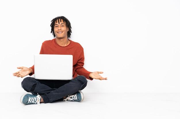 Jeune homme afro-américain assis sur le sol et travaillant avec son ordinateur portable souriant