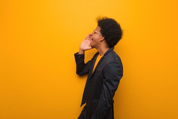 Jeune homme afro-américain au-dessus d'un mur orange chuchotant une rumeur de potins