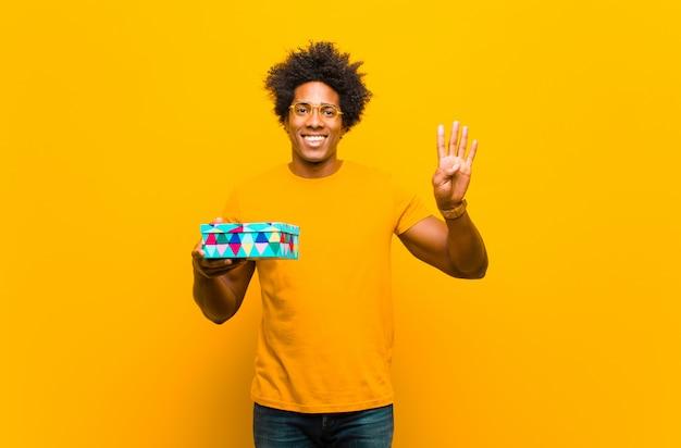 Jeune homme afro-américain avec une boîte cadeau contre orange arr.plans