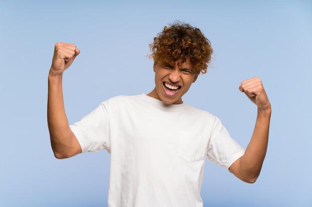 Jeune homme afro-américain avec une chemise blanche célébrant une victoire