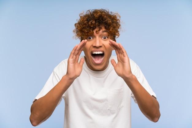 Jeune homme afro-américain avec une chemise blanche en criant avec la bouche grande ouverte