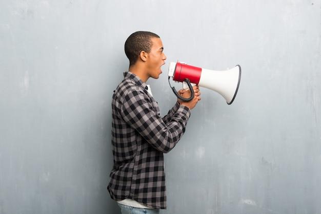 Jeune homme afro-américain avec une chemise à carreaux criant à travers un mégaphone