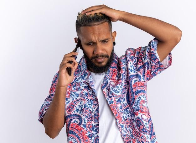 Jeune homme afro-américain en chemise colorée semblant confus tout en parlant au téléphone portable debout sur blanc
