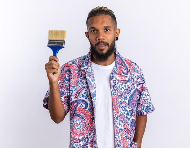 Jeune homme afro-américain en chemise colorée tenant un pinceau regardant la caméra avec un visage sérieux debout sur blanc