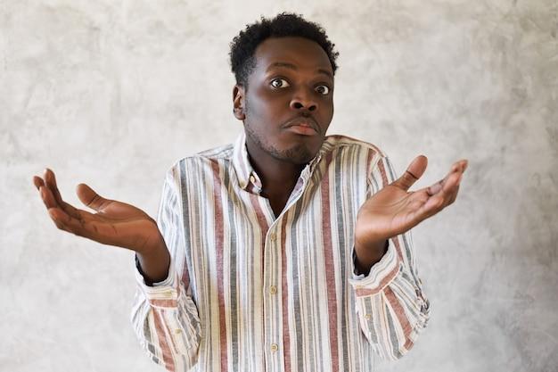 Un jeune homme afro-américain désemparé étant perdu en haussant les épaules en disant que je ne sais pas.