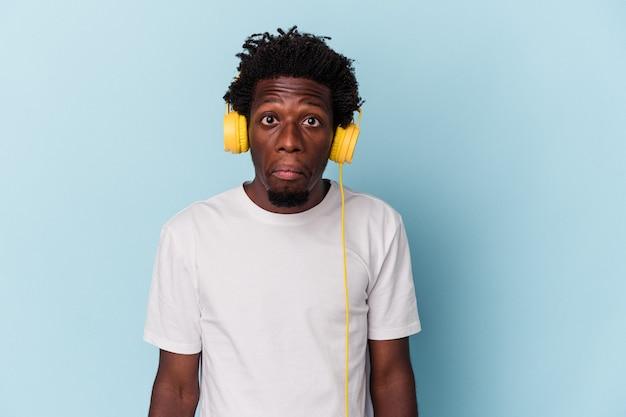 Jeune homme afro-américain écoutant de la musique isolée sur fond bleu hausse les épaules et ouvre les yeux confus.