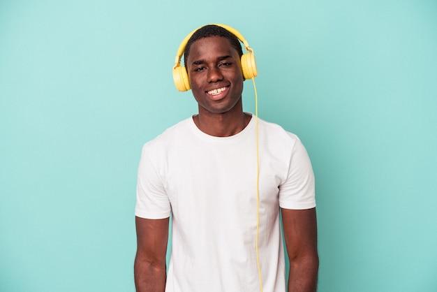 Jeune homme afro-américain écoutant de la musique isolée sur fond bleu heureux, souriant et joyeux.