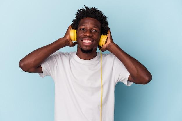 Jeune homme afro-américain écoutant de la musique isolée sur fond bleu levant le poing après une victoire, concept gagnant.