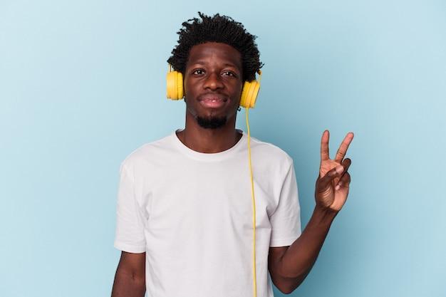 Jeune homme afro-américain écoutant de la musique isolée sur fond bleu montrant le numéro deux avec les doigts.