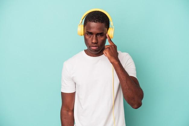 Jeune homme afro-américain écoutant de la musique isolée sur fond bleu pointant le temple avec le doigt, pensant, concentré sur une tâche.