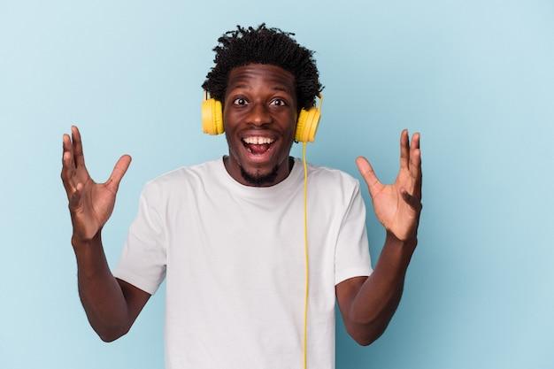 Jeune homme afro-américain écoutant de la musique isolée sur fond bleu recevant une agréable surprise, excité et levant les mains.