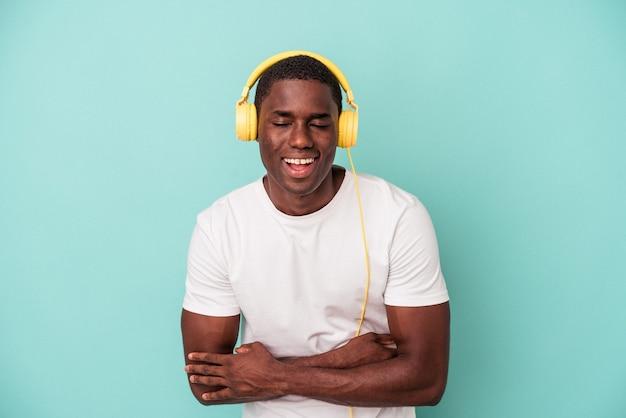 Jeune homme afro-américain écoutant de la musique isolée sur fond bleu en riant et en s'amusant.