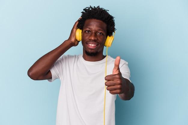 Jeune homme afro-américain écoutant de la musique isolée sur fond bleu touchant l'arrière de la tête, pensant et faisant un choix.