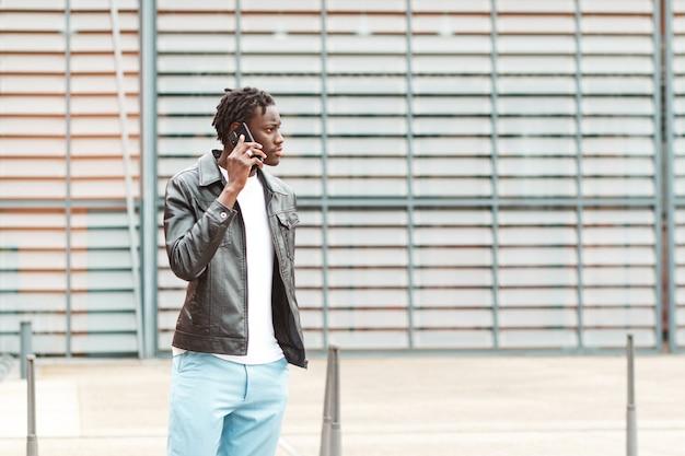 Jeune homme afro-américain élégant parlant au téléphone dans les rues de lyon en france